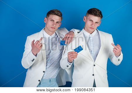 Businessmen showing middle fingers in white jackets. Cooperation and partnership. Men holding blank cards on blue background. Business communication and meeting. Banking and saving concept.