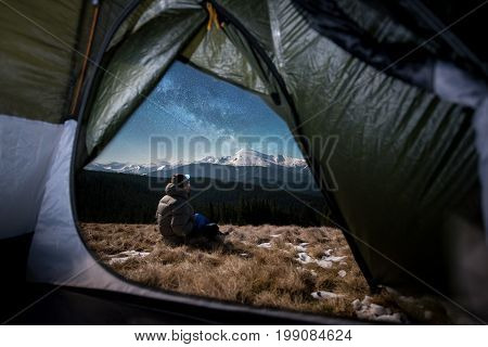 View From Inside A Tent On The Male Hiker Have A Rest In His Camping At Night. Man With A Headlamp S
