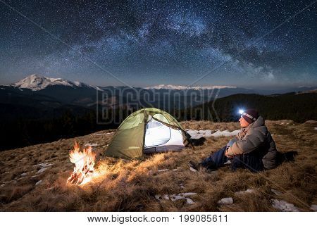 Male Tourist Have A Rest In His Camp At Night. Guy With A Headlamp Sitting Near Campfire And Tent Un