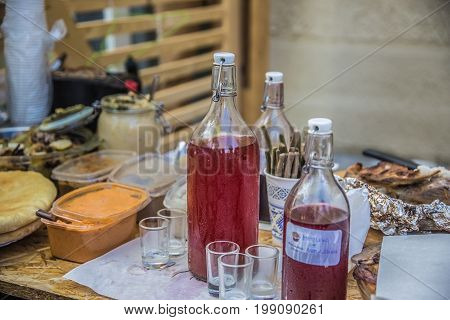 A loaf of bread jam and a bottle of alcoholic tincture on a table laid for guests