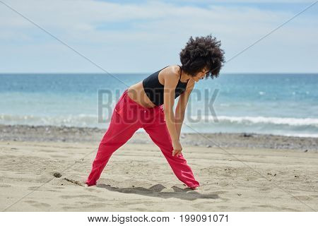 Young Afro American Sportswoman Warming Up On Beach
