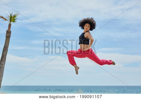 Young Sportswoman Jumping On Beach With Hands On Waist