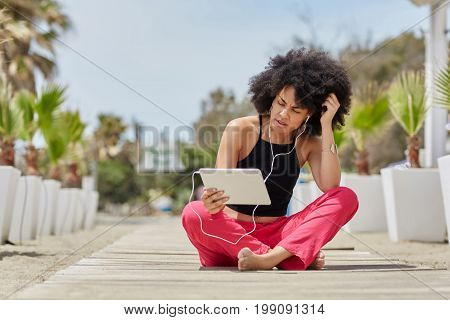 Afro American Woman Sitting Crossed Legs Outside Using Tablet