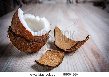 On the light surface of the table is one half the coconut in the hairy shell close up. Next to the coconut are the remains of a shaggy shell.