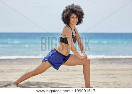 Pretty Afro American Sportswoman Stretching Out On Beach