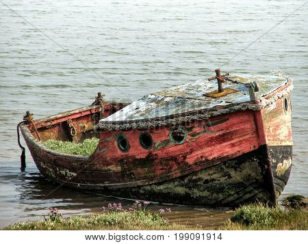 old wooden wrecked boat with faded red and black paint on the edge of a riverbank with rotten planks and vegetation