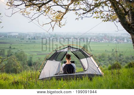 Rear View Of Woman Sitting In A Tent On Top Of A Hill Using Her Laptop While Camping Lifestyle Activ