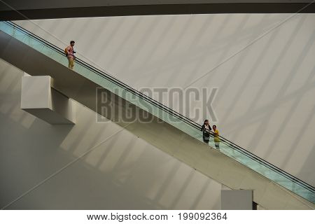 People Standing On Escalator In Shopping Mall