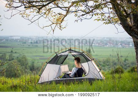 Shot Of A Female Sitting In A Tent On Top Of A Hill Using Her Laptop While Camping Lifestyle Active
