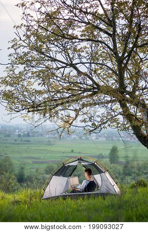 Vertical Shot Of A Woman Sitting In A Tent On Top Of A Hill Under Tree Using Her Laptop While Campin