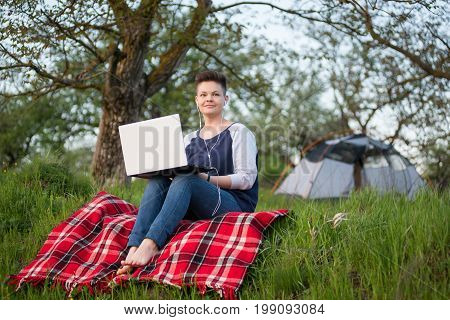 Young Woman Sitting On The Grass In Front Of Her Tent Working On A Laptop While Camping Nature Peace