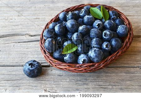Freshly picked blueberries in a basket on old wooden background.Fresh blueberries with green leaves on rustic table.Blueberry. Bilberry.Healthy eating,diet and nutrition concept.Selective focus.