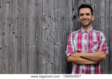Portrait of handsome young man in shirt keeping arms crossed and smiling while standing against wooden background.