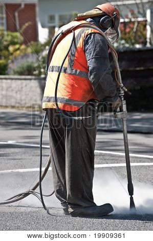 Road worker sandblasting on the road