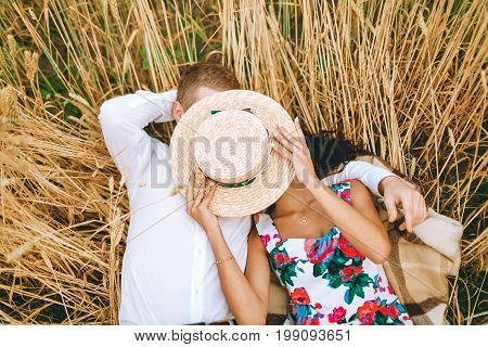 Young Couple Is Lying On A Field And Covers Their Faces By The Straw Hat