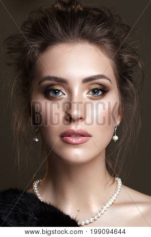 Portrait of beautiful young woman with professional makeup, perfect skin, volume hairdo in pearl jewelry on dark background. Trendy golden smoky eyes. Retro style