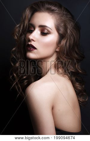 Portrait of beautiful young woman with professional makeup, perfect skin, red lips, volume wavy hairstyle on dark background. Trendy bronze smoky eyes.