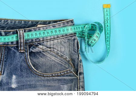Losing Weight Concept: Measure Tape Around Jeans