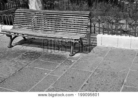 one old wooden bench for rest in the square and untidy garbage nearby monochrome tone
