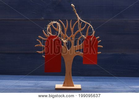 Organizer for jewellery made of wood on dark blue vintage background. Decorative tree to store jewellery. Beauty and shopping concept. Earring holder with red price tags close up.