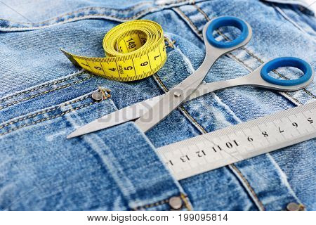 Metal scissors ruler and measure tape on denim pants. Tailoring and design concept. Tailors tools with denim fabric selective focus. Things for making clothes in back pocket of jeans close up.