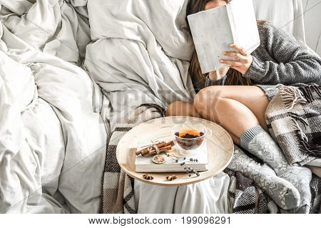 Cute girl on a comfortable chair with tea , reading a book, the concept of comfort and hipster