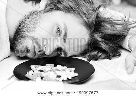 Pills on plate near motionless guy with beard. Man with open eyes and empty sight lies on light wooden background. Drugs in capsules and round colored tablets. Overdose or unhealthy treatment concept