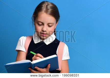 School Girl With Diligent Face Expression On Blue Background