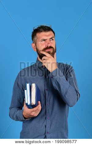 Teacher wears glasses and holds organizers. Notebook in blue color in guys hand isolated on blue background. Professor with thinking face expression. Knowledge concept: man with beard and books