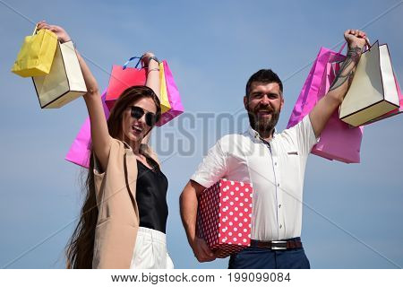 Couple Holds Colorful Packets Up On Blue Sky Background