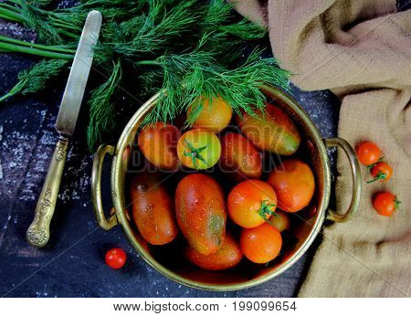 fresh tomatoes with dill in a bronze bowl