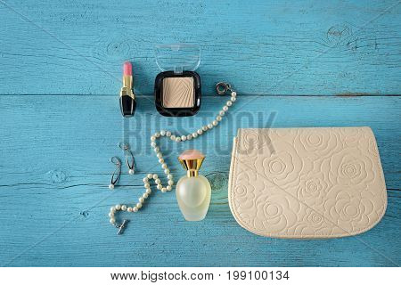 Cosmetics perfumes jewelry made of pearls and handbag on an old wooden background of blue color