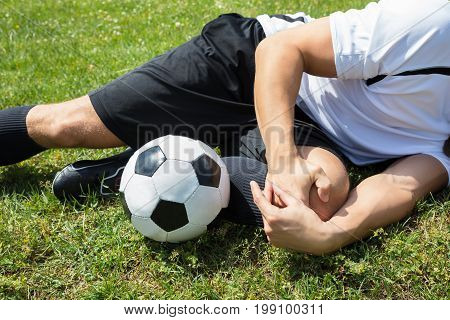 Close-up Of Male Soccer Player Suffering From Knee Injury Lying On Field