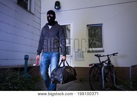 Burglar In Black Mask Escaping With Handbag After Stealing From House