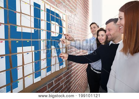 Business People Looking At Hr Text Made With Adhesive Notes On Corkboard In Office