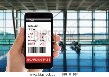 Cropped image of woman's hand holding smart phone with electronic boarding pass in airport