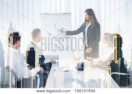 Double exposure of businesswoman giving presentation to colleagues amidst buildings