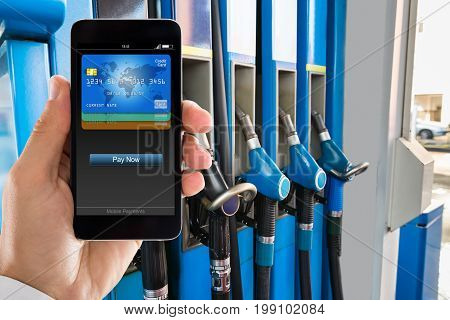 Closeup of man paying with smartphone at gas station