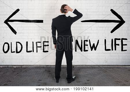 Rear view of confused businessman looking at arrow signs above old and new life text