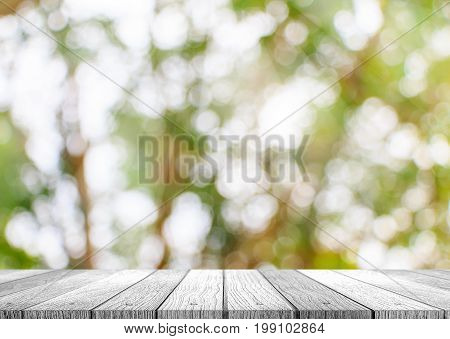 Wooden plank tabletop with fresh blurred nature green background use for products or something display or showing