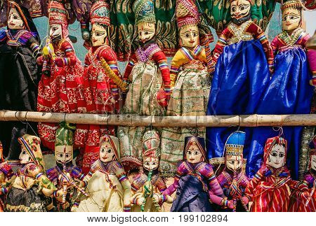 Colorful handcrafted dolls in traditional costumes of India. Marketplace with old style indian toys for children.