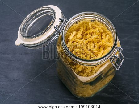 Photo of fusilli pasta in an open jar on top of a slate background.