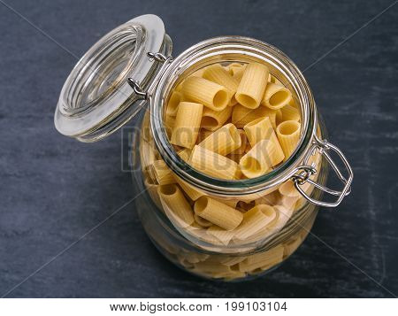 Photo of Mezzi Rigatoni in an open jar on top of a slate background.