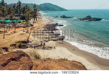 Sandy beach with green hills palm trees tourist relaxing in waves of Indian ocean, Goa state, India.