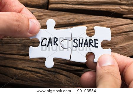 Closeup of hands connecting car share jigsaw pieces against wood