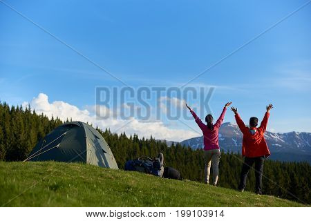 Rearview Shot Of Two Happy Female Hikers Embracing Morning Sun On Top Of A Hill Standing With Their