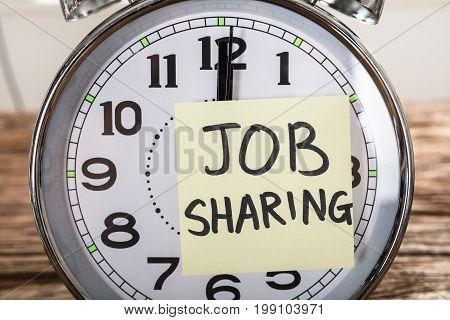 Closeup of job sharing adhesive note stuck on alarm clock on wood