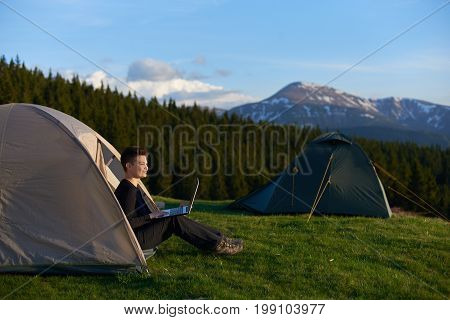 Happy Girl Enjoying Sunrise In The Mountains Sitting In Her Tent Working On The Laptop Copyspace Cam