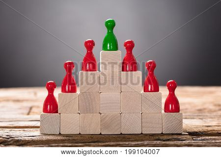 Closeup of green and red pawn figurines arranged on wooden blocks