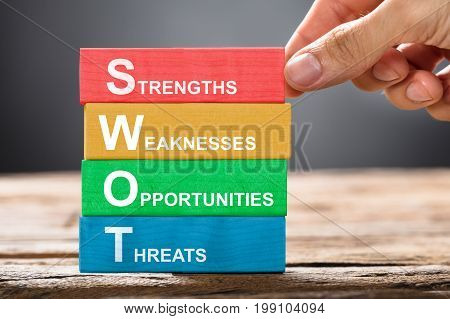 Closeup of hand building colorful SWOT concept with wooden blocks on wood